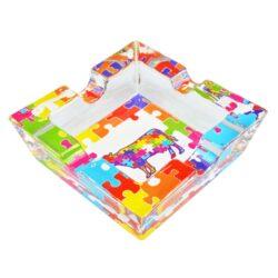 Cigaretový popelník skleněný Puzzle-Cigaretový popelník skleněný Puzzle. Hranatý popelník na cigarety se čtyřmi odkládacími místy je vyrobený ze silného skla. Díky větší šířce dvou odkládacích míst, je tento popelník vhodný také pro doutníky. Tloušťka stěny je 1,4cm. Dno popelíku je potištěné atraktivním barevným motivem. Rozměry popelníku: 10x10x3,1cm. Popelník je dodávaný v kartonové krabičce.