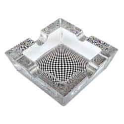 Cigaretový popelník skleněný Cubes-Cigaretový popelník skleněný Cubes. Hranatý popelník na cigarety se čtyřmi odkládacími místy je vyrobený ze silného skla. Díky větší šířce dvou odkládacích míst, je tento popelník vhodný také pro doutníky. Tloušťka stěny je 1,4cm. Dno popelíku je potištěné atraktivním barevným motivem. Rozměry popelníku: 10x10x3,1cm. Popelník je dodávaný v kartonové krabičce.