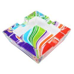 Cigaretový popelník skleněný Rainbow-Cigaretový popelník skleněný Rainbow. Hranatý popelník na cigarety se čtyřmi odkládacími místy je vyrobený ze silného skla. Díky větší šířce dvou odkládacích míst, je tento popelník vhodný také pro doutníky. Tloušťka stěny je 1,4cm. Dno popelíku je potištěné atraktivním barevným motivem. Rozměry popelníku: 10x10x3,1cm. Popelník je dodávaný v kartonové krabičce.