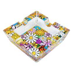 Cigaretový popelník skleněný Flowers-Cigaretový popelník skleněný Flowers. Hranatý popelník na cigarety se čtyřmi odkládacími místy je vyrobený ze silného skla. Díky větší šířce dvou odkládacích míst, je tento popelník vhodný také pro doutníky. Tloušťka stěny je 1,4cm. Dno popelíku je potištěné atraktivním barevným motivem. Rozměry popelníku: 10x10x3,1cm. Popelník je dodávaný v kartonové krabičce.