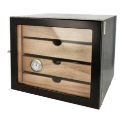 Humidor na doutníky Cabinett černý 60D, stolní-Atraktivní stolní humidor na doutníky Angelo Cabinett s kapacitou cca 60 doutníků. Kvalitně zpracovaný humidor s pololesklým povrchem v černém provedení a prosklenými dvířky. Humidor je vybavený třemi šuplíky s přepážkami (vnitřní rozměry 20,5x17,5x3,3cm) s podélnými otvory ve dně a jedním nižším šuplíkem (vnitřní rozměry 20,5x17,5x1,6cm) s plným dnem. Součástí balení humidoru je vyměnitelný vlhkoměr a 4x polymerový zvlhčovač. Průměr otvoru pro zvlhčovač je 3,55cm. Dvířka uchycená na panty se zavírají na zámek. Vnitřek humidoru je vyložený cedrovým dřevem. Rozměr celého humidoru: 24,5x22x23cm.  Humidory jsou dodávány nezavlhčené, proto Vám nabízíme bezplatnou volitelnou službu Zavlhčení humidoru, kterou si vyberete v Souvisejícím zboží. Nový humidor je nutné před prvním uložením doutníků zavlhčit, upravit a ustálit jeho vlhkost na požadovanou hodnotu. Dobře zavlhčený humidor uchová Vaše doutníky ve skvělé kondici.