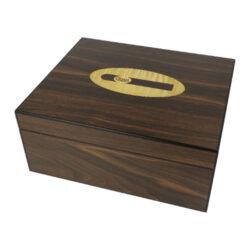 Humidor na doutníky Cigar logo ořech-Stolní humidor na doutníky Cigar logo s kapacitou cca 25 doutníků dle velikosti. Atraktivní humidor je ve tmavě hnědém ořechovém odstínu v matném provedení. Na horní straně víka je umístěné logo Cigar. Humidor je vybavený jednou přepážkou, kterou je možné rozdělit prostor pro doutníky. Součástí balení humidoru je vlhkoměr a polymerový zvlhčovač včetně oboustranné samolepky pro uchycení. Vnitřek humidoru je vyložený cedrovým dřevem. Rozměr celého humidoru: 26x22x11 cm.  Průměr vlhkoměru: 5 cm  Humidory jsou dodávány nezavlhčené, proto Vám nabízíme bezplatnou volitelnou službu Zavlhčení humidoru, kterou si vyberete v Souvisejícím zboží. Nový humidor je nutné před prvním uložením doutníků zavlhčit, upravit a ustálit jeho vlhkost na požadovanou hodnotu. Dobře zavlhčený humidor uchová Vaše doutníky ve skvělé kondici.