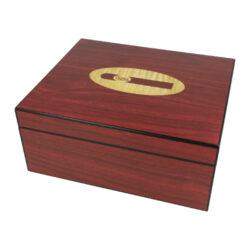 Humidor na doutníky Cigar logo rosewood-Stolní humidor na doutníky Cigar logo s kapacitou cca 25 doutníků dle velikosti. Atraktivní humidor je ve tmavě bordovém matném provedení s logem Cigar na horní straně víka. Humidor je vybavený jednou přepážkou, kterou je možné rozdělit prostor pro doutníky. Součástí balení humidoru je vlhkoměr a polymerový zvlhčovač včetně oboustranné samolepky pro uchycení. Vnitřek humidoru je vyložený cedrovým dřevem. Rozměr celého humidoru: 26x22x11 cm.  Průměr vlhkoměru: 5 cm  Humidory jsou dodávány nezavlhčené, proto Vám nabízíme bezplatnou volitelnou službu Zavlhčení humidoru, kterou si vyberete v Souvisejícím zboží. Nový humidor je nutné před prvním uložením doutníků zavlhčit, upravit a ustálit jeho vlhkost na požadovanou hodnotu. Dobře zavlhčený humidor uchová Vaše doutníky ve skvělé kondici.