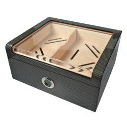 Humidor na doutníky Carbon Glasstop Digi-Stolní humidor na doutníky Carbon Glasstop Digi s kapacitou cca na 40 - 50 doutníků (v závislosti na velikosti). Atraktivní humidor s průhledným víkem s výplní z akrylu je ve tmavém karbonovém provedení. Exklusivní vzhled humidoru dává povrch ve vysokém lesku. Variabilitu rozdělení prostoru pro doutníky zajišťuje vnitřní stavitelná přepážka s místem pro doutníkové příslušenství nebo zvlhčovač a horní vyndavací patro též rozdělitelné pomocí přepážky. Pod tímto patrem je možné doutníky skladovat nejen jednotlivě, ale také po celém balení. Celý prostor humidoru na doutníky je vyložený cedrovým dřevem, které prospívá skladování doutníků. Precizně zpracovaný humidor je vybavený polymerovým zvlhčovačem a výměnným digitálním vlhkoměrem, který je zasunutý v čelní části. Digitální vlhkoměr je napájený 1x knoflíkovou baterií LR 44 1,5 V. Na displeji zobrazuje aktuální vlhkost v humidoru (RH nebo RT) a teplotu (°C nebo °F). Poškrábání povrchu, na kterém je humidor položený, zabraňuje jemná sametová látka, kterou je spodní vnější část vybavena.  Rozměry humidoru vnější: 32x27,5x15 cm Vnitřní prostor pro doutníky: 27x23x10,5 cm Vnitřní rozměry horního patra: 26,5x21,5x4,3 cm Průměr otvoru pro vlhkoměr: 4,2 cm  Humidory jsou dodávány nezavlhčené, proto Vám nabízíme bezplatnou volitelnou službu Zavlhčení humidoru, kterou si vyberete v Souvisejícím zboží. Nový humidor je nutné před prvním uložením doutníků zavlhčit, upravit a ustálit jeho vlhkost na požadovanou hodnotu. Dobře zavlhčený humidor uchová Vaše doutníky ve skvělé kondici.