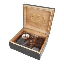 Humidor na doutníky SET 25, černý, 26x22,5x10,5cm-Stolní humidor na doutníky SET s kapacitou cca na 25 doutníků (v závislosti na velikosti). Praktická sada obsahující humidor a doutníkové příslušenství, které jistě ocení každý kuřák doutníků. Doutníkový set obsahuje mimo humidoru doutníkový popelník s kovovou vložkou, plastový doutníkový ořezávač v černém provedení a černé koženkové pouzdro na dva doutníky. Elegantní humidor je v černé barvě s pololesklým povrchem. Na vnitřní straně víka najdeme prostor pro uchycení vyměnitelného vlhkoměru a zvlhčovače s houbou, které jsou součástí balení včetně samolepících pásků se suchým zipem, za které se uchytí. Prostor pro doutníky je možné rozdělit dle potřeby přiloženou přepážkou. Vnitřek humidoru je vyložený cedrovým dřevem, které prospívá skladování doutníků. Poškrábání povrchu, na kterém je humidor položený, zabraňuje jemná sametová látka, kterou je spodní vnější část humidoru vybavena. Ideální sada vhodná jako dárek pro začínajícího kuřáka doutníků.  Rozměry humidoru vnější (Š x H x V): 260 x 225 x 105 mm Prostor pro doutníky (Š x H x V): 236 x 197 x 71 mm Délka/průměr otvoru ořezávače: 91 mm/20 mm Rozměry popelníku (Š x H x V): 18 x 95 x 25 mm Průměr otvoru pro zvlhčovač: 57,5 mm Průměr otvoru pro vlhkoměr: 38 mm Pouzdro na doutníky - vnější rozměry(zcela zavřené) (Š x H x V): 173 x 65 x 25 mm  Pouzdro na doutníky - průměr otvorů/vnitřní možný prostor(délka) pro doutníky: 19 mm/180 mm  Humidory jsou dodávány nezavlhčené, proto Vám nabízíme bezplatnou volitelnou službu Zavlhčení humidoru, kterou si vyberete v Souvisejícím zboží. Nový humidor je nutné před prvním uložením doutníků zavlhčit, upravit a ustálit jeho vlhkost na požadovanou hodnotu. Dobře zavlhčený humidor uchová Vaše doutníky ve skvělé kondici.  a target=_blank href=..\www\prilohy\Návod_k_použití_humidoru.pdfNávod k použití humidoru - PDF/a