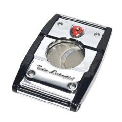 Doutníkový ořezávač Lamborghini Precisione, chrom-černý-Elegantní ořezávač na doutníky Tonino Lamborghini Precisione. Silné tělo dvoubřitého ořezávače je precizně vyrobené z kvalitní nerezové oceli. Jednoduchým stisknutím tlačítka dolů, které současně slouží jako pojistka proti otevření, uvolníte čepele od sebe a ořezávač je připraven k použití. Dvojité velmi ostré gilotinové nože, jsou zárukou rychlého a čistého řezu doutníku. Doutníkový ořezávač je dodáván v kožené krabičce vyložené jemným sametem. Rozměry zavřeného ořezávače: 6,5x4cm.