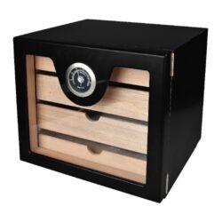 Humidor na doutníky Cabinett Black na 60 doutníků, stolní-Stolní humidor na doutníky s kapacitou cca 60 doutníků. Kvalitně zpracovaný humidor s černým pololesklým povrchem a prosklenými dvířky. Humidor je vybavený třemi šuplíky s přepážkami (vnitřní rozměry 20,5x17,5x3,3cm) s podélnými otvory ve dně a jedním nižším šuplíkem (vnitřní rozměry 20,5x17,5x1,5cm) s plným dnem. Součástí balení humidoru je výměnitelný vlhkoměr a polymerový zvlhčovač. Dvířka uchycená na panty se zavírají se na magnet. Vnitřek humidoru je vyložený cedrovým dřevem. Rozměr celého humidoru: 22,5x24,5x23cm.  Humidory jsou dodávány nezavlhčené, proto Vám nabízíme bezplatnou volitelnou službu Zavlhčení humidoru, kterou si vyberete v Souvisejícím zboží. Nový humidor je nutné před prvním uložením doutníků zavlhčit, upravit a ustálit jeho vlhkost na požadovanou hodnotu. Dobře zavlhčený humidor uchová Vaše doutníky ve skvělé kondici.