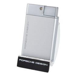 Doutníkový zapalovač Porsche Design P3631, stříbrný-Luxusní doutníkový zapalovač značky Porsche Design. Exklusivitu zapalovači dává nejen logo Porsche Design na přední straně, ale především precizní výroba, kvalitně zpracovaný povrch a neotřelé barevné provedení. Tryskový zapalovač Porsche Design na doutníky obsahuje ve spodní části integrovaný vyštípávač, nastavení intenzity plamene a plnící ventil. Stisknutím tlačítka se odklopí horní kryt a dojde k zapálení dvou trysek. Doutníkový zapalovač je dodáván v dárkové krabičce. Výška: 6,5cm.