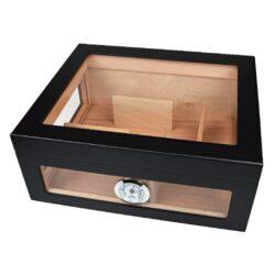 Humidor na doutníky černý 75D, stolní-Moderní stolní humidor na doutníky s kapacitou cca 75 doutníků (v závislosti na velikosti). Prosklený humidor v černé matné barvě je dodáván s vlhkoměrem a polymerovým zvlhčovačem. Prostor pro doutníky je variabilní díky čtyřem magnetickým příčkám, které lze libovolně podle potřeby rozmístit. Vnitřek humidoru je vyložený cedrovým dřevem. Rozměr humidoru: 32x27,5x13 cm.  Humidory jsou dodávány nezavlhčené, proto Vám nabízíme bezplatnou volitelnou službu Zavlhčení humidoru, kterou si vyberete v Souvisejícím zboží. Nový humidor je nutné před prvním uložením doutníků zavlhčit, upravit a ustálit jeho vlhkost na požadovanou hodnotu. Dobře zavlhčený humidor uchová Vaše doutníky ve skvělé kondici.